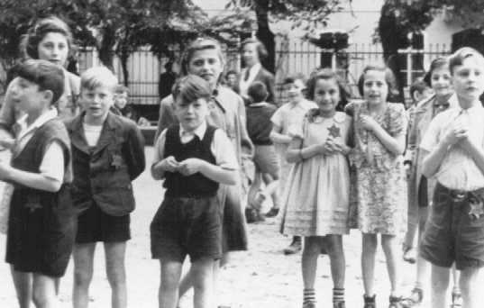 "A photograph of Jewish children in the Theresienstadt ghetto taken during an inspection by the International Red Cross. Prior to this visit, the ghetto was ""beautified"" in order to deceive the visitors. Czechoslovakia, June 23, 1944."